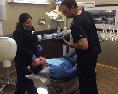 Carlsbad tooth veneer dentists Dr. Stephen Dankworth and his wife Kimberly applying porcelain dental veneers to an Encinitas patient's tooth.